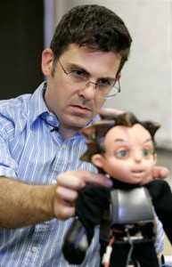 Creator David Hanson is shown making an adjustment to the robot prior to an interview.