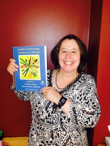 Dr. Willkomm holds up her latest book on assistive technology solutions