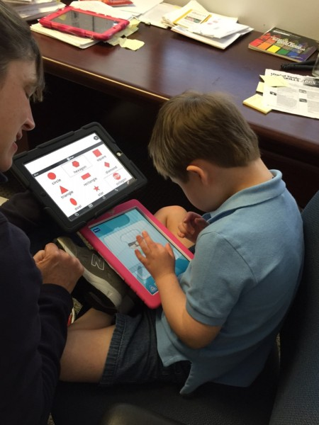 Boy on tablet with teacher