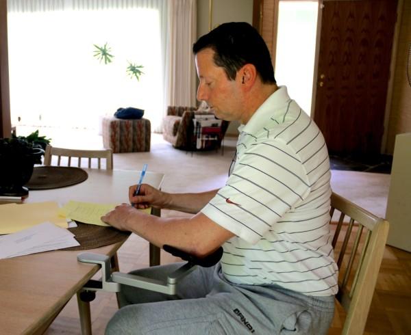 Victor using arm brace to write