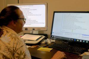 Linda using large screen monitior at desk