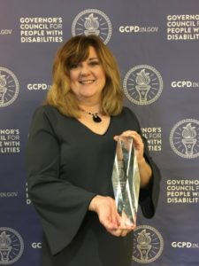 Stacey holding the Champions of Inclusion Award