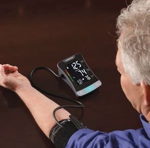 Man with blood pressure monitor cuff on his arm