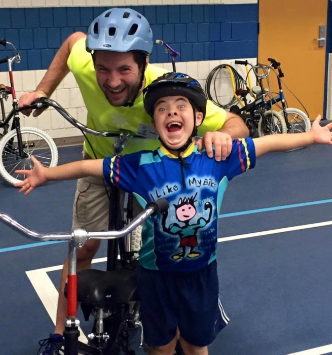 child with volunteer for i can bike program