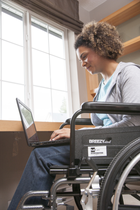 Woman using computer and sitting in a wheelchair