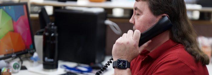 Randy Berg answering phone at his desk