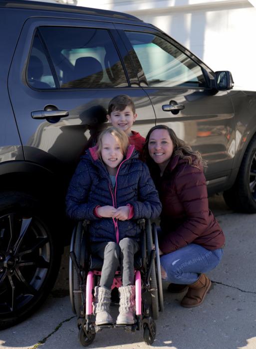Sara beside her vehicle with her children