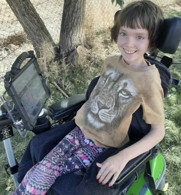 young girl in wheelchair with communication device mounted to wheelchair